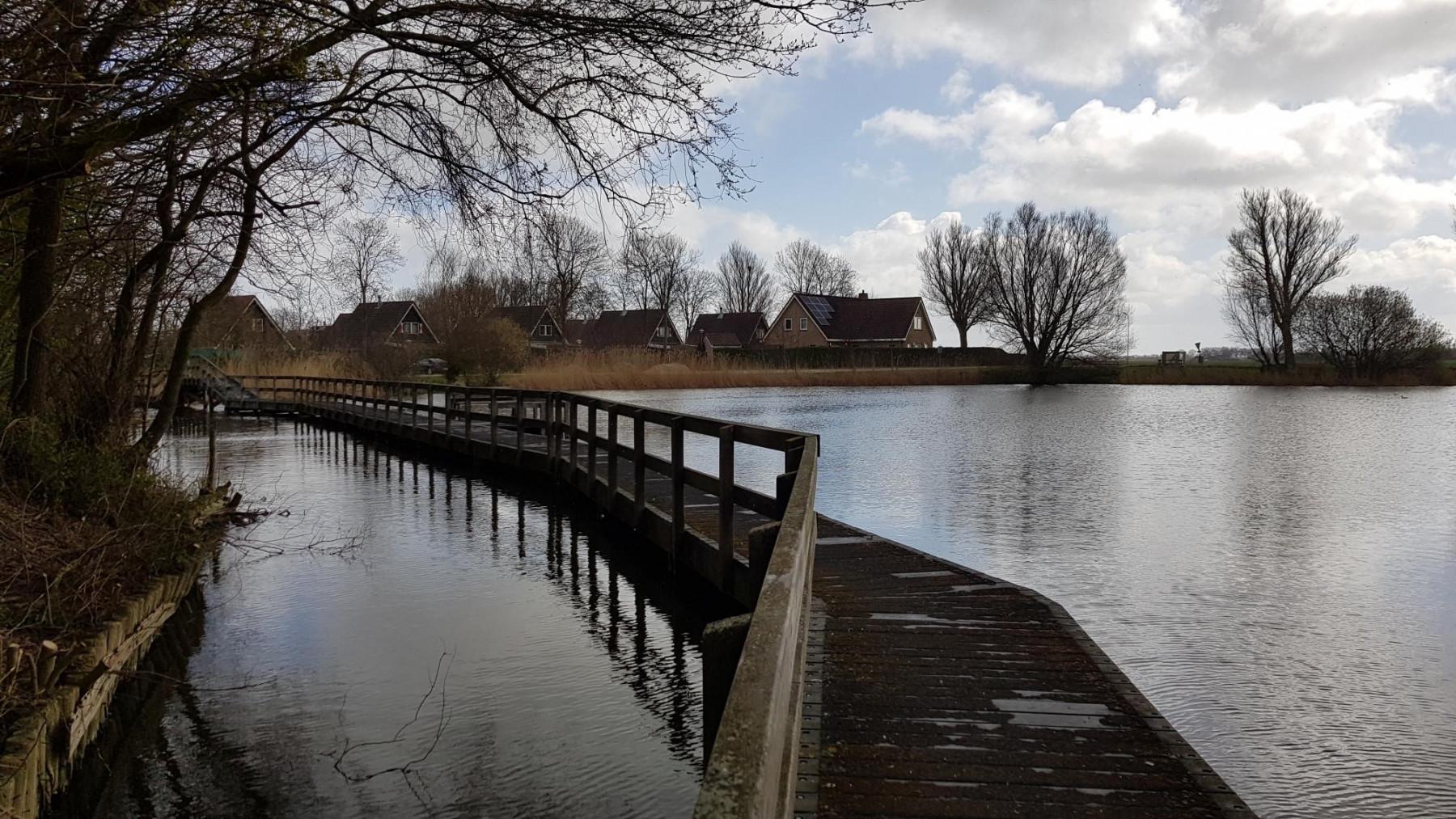 Einer der beiden Seen vor dem Park mit einer Holzbrücke